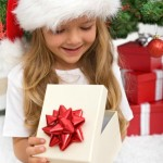 Little girl opening present in front of christmas tree - closeup