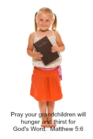 The little girl with holy bible. Studio shot on white background.
